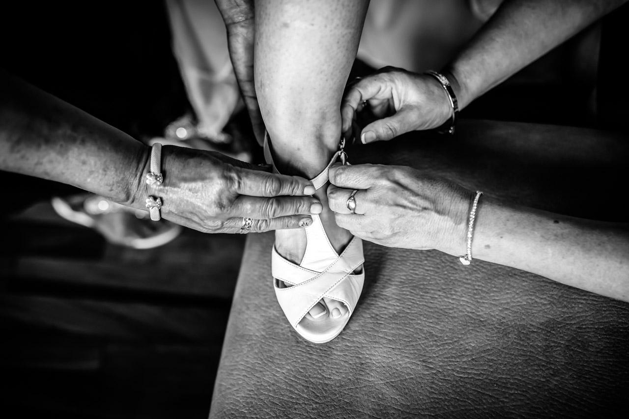 madre de la novia y dos amigas atandoles los zapatos