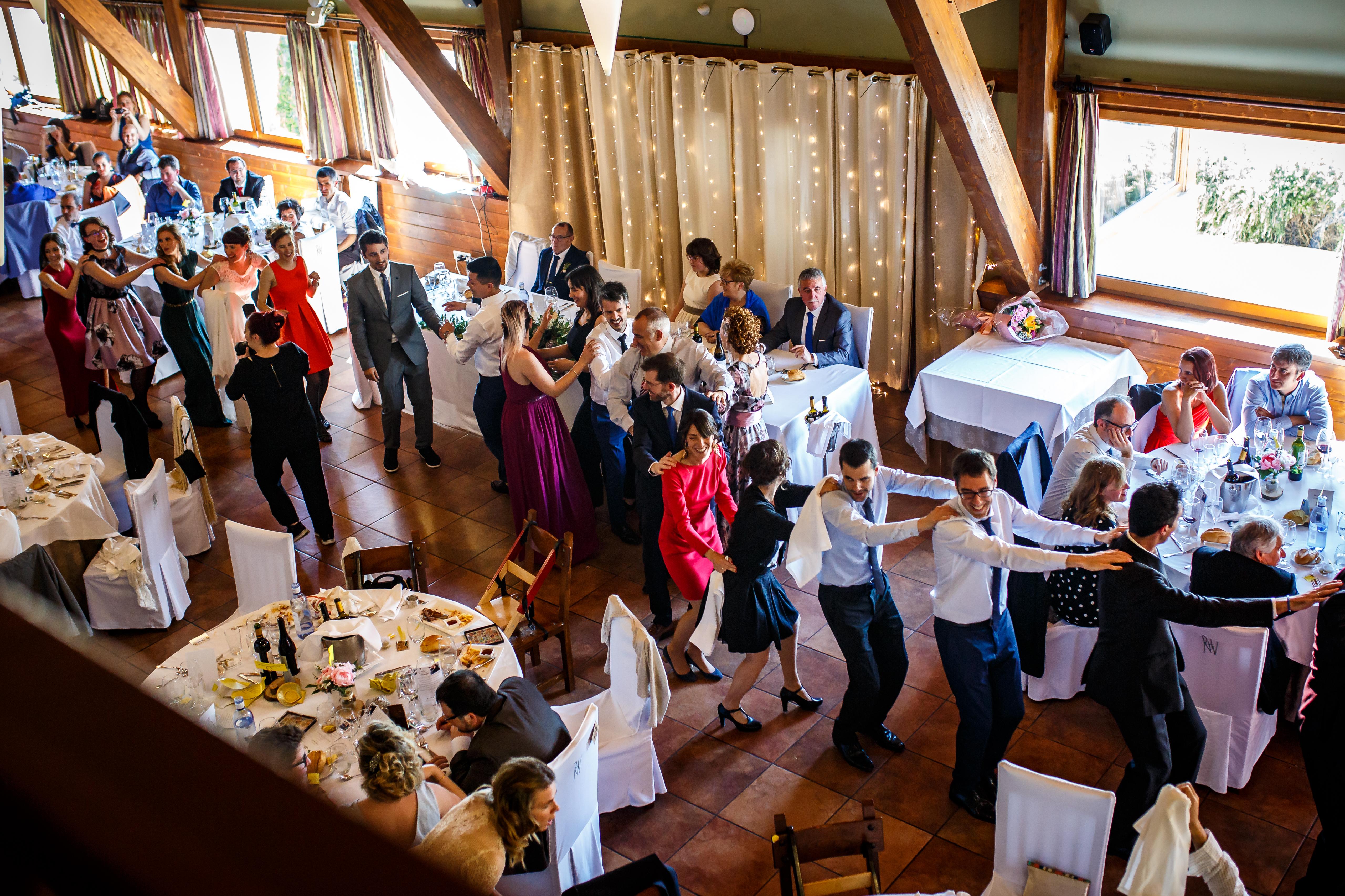 los invitados de la boda bailan una conga en mitad del banquete en una boda en laguardia