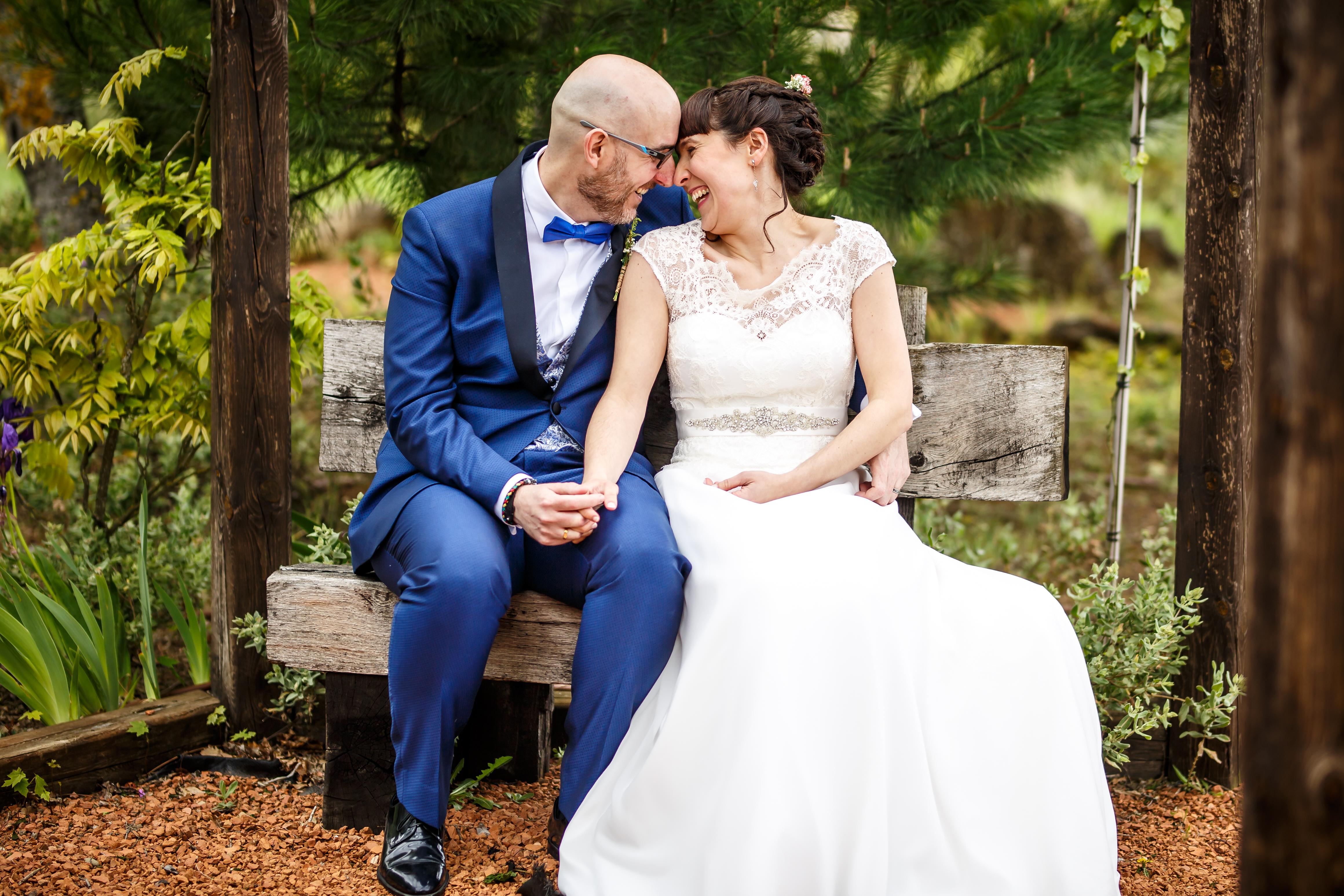 los novios sonríen sentados en un banquito en una boda en laguardia