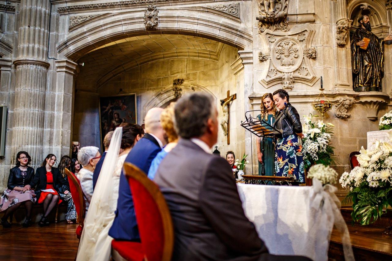 dos amigas de la novia leen durante la ceremonia en una boda en laguardia
